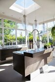 Elegant kitchen island in light-flooded interior with pendant lamps above counter and skylight