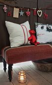 Shiny red teddy bear and cushions on bench upholstered with Norwegian flag pattern below garland of Christmas decorations