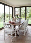 Dining table and white cane chairs in conservatory with tiled floor