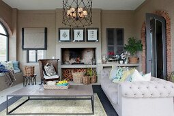 Grey sofa and coffee table on loggia with fireplace