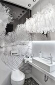 Minimalist washstand with marble counter and artistic wall decoration in white designer bathroom