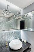 Spherical sink on granite counter against mosaic-tiled wall below designer lamps