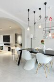 Various classic chairs around black table below pendant lamps next to wide rounded archway in open-plan interior