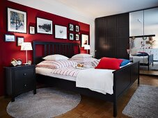 A bedroom with dark wooden furniture and pictures hung on dark red wall