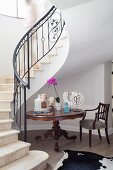Sculptures on Baroque table at foot of elegantly winding staircase in foyer