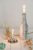 Festive arrangement of origami candlestick and bottle covered in newspaper on table