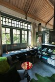 Table, shell chairs and crockery on sideboard in converted stables with wooden ceiling and doors