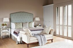 Antique bench at foot of double bed with tall headboard in elegant, country-house-style bedroom