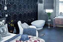 Bedroom with free-standing bathtub in open-plan ensuite bathroom, ornate wallpaper and white armchair next to bed