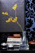 Stacked books, tealight holders and yellow Anigozanthos in glass vase on surface against wall covered in ornate wallpaper