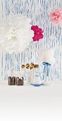 Decorated afternoon coffee table - paper pompoms, table lamp with doily lampshade, cake pops and packaged coffee beans against blue stripes back wall