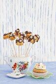 Cake pops stood in vintage sugar bowl next to cupcake