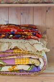 Colourful folded quilts in a wooden cupboard