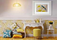 White console table next to stack of cushions and Thonet chair against wall with yellow wallpaper below dado rail