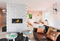 Fireplace in hollow-brick wall, leather sofa, coffee tables and sleeping area on platform in open-plan interior