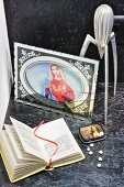 Picture of Mary, sweet tin with picture of Jesus on lid, open bible and lemon squeezer on black-painted chipboard panel