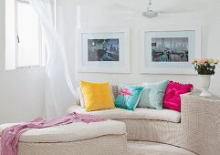 Curved, pale wicker sofa and matching ottoman with colourful scatter cushions on seat cushions in corner below framed pictures on wall