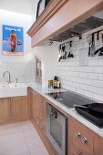 L-shaped kitchen counter in pale wood with marble counter and mantel hood over cooker