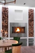 Dining set in front of fire in fireplace flanked by firewood in niches
