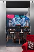 Leopard-print chairs around table in dining room painted grey with modern artwork on wall