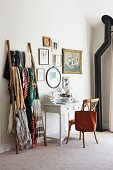 Collection of scarves, white vintage bureau, gallery of vintage pictures and black stove pipe in corner of feminine room