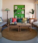 Wooden tables on round sisal rug in front of cushions on bench and ornaments in green-painted niche