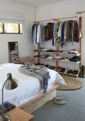Clothes rails with shelves in simple bedroom