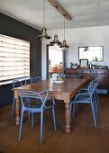 Blue-painted chairs with curved backrests around wooden table below pendant lamps