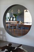 View of dining table and chairs seen through round aperture in wall