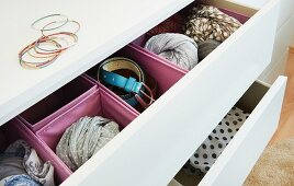 Pink boxes in an open drawer for accessories