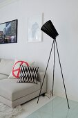 Black studio lamp next to white couch in elegant living room