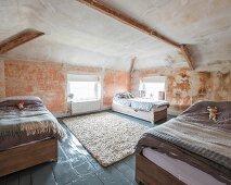 Drei Betten mit Kuscheltier in renoviertem, historischem Dachraum mit Wand-Patina