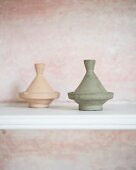 Two pastel tagine-shaped ornaments on white shelf
