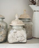 Vintage jars with patinated lids and enamel jug in background