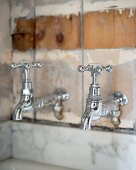 Retro-style taps mounted on patinated board wall above strip of marble cladding