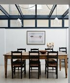 Rustic wooden dining table and chairs in extension with glass roof
