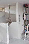 Head of staircase with white, solid balustrade and bookcase to one side