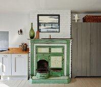 Vintage range in masonry fireplace painted green next to kitchen counter in rustic interior