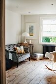 Antique sofa next to classic table lamp on vintage table in rustic living room with wooden floor