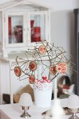 Branches in vase with garland of stamped wooden discs as festive table decoration