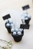 Plant pots painted black and decorated with baubles and feathers as festive table ornaments