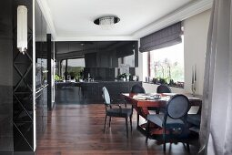 Dining area with antique chairs in elegant living room with black, fitted cupboards, dark wooden floor and white stucco frieze