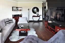 Pale grey couch, elegant coffee table and Art Deco sideboard in open-plan living area