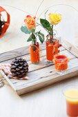 Rosen in Glasvasen dekoriert mit orangefarbenen Vasenmanschetten aus Filz