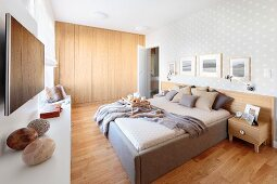 Bedroom with double bed on pale wooden floor and fitted, flat-fronted wooden wardrobes