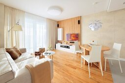 Dining set with white chairs at wooden table and pale sofa in open-plan, modern interior