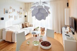 Designer pendant lamp with white leaves above round dining table and pale sofa in background in modern interior