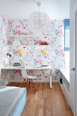 Desk, classic chair and floral wallpaper in narrow teenager's bedroom