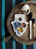Pots of spices on hamsa-shaped tray, paintbrushes and shells on old wooden tray
