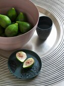 Beaker, green figs in bowl and cut fig on plate on silver tray